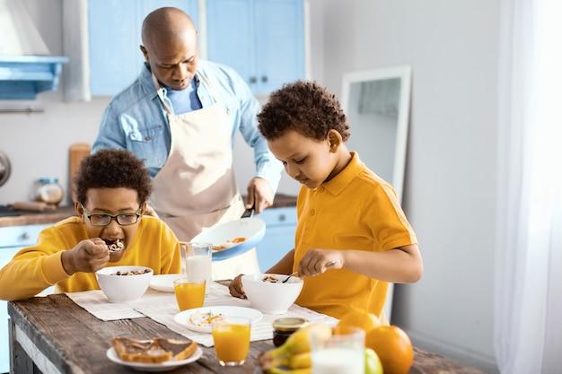 おいしい朝食。エプロンを着た父親がオムレツを調理している間、朝食にシリアルを食べる愛らしい男の子