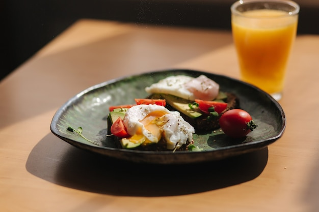 Вкусный завтрак дома. сэндвич со свежими ломтиками авокадо над ржаным тостом с помидорами черри и яйцом-пашот на зеленой тарелке. свежевыжатый апельсиновый сок желток течет на тосте