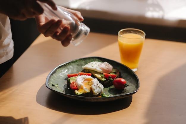 Вкусный завтрак дома. женщина-соль сэндвич со свежим нарезанным авокадо над ржаным тостом с помидорами черри и яйцом-пашот на зеленой тарелке. свежевыжатый апельсиновый сок на тосте течет желток.