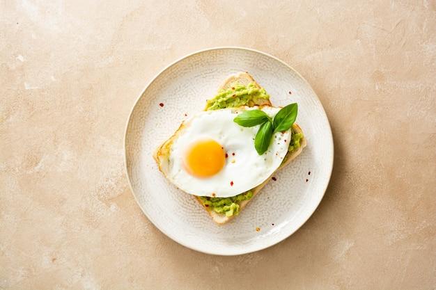 Вкусный завтрак. гренки с авокадо и жареные яйца. здоровая еда, вид сверху.