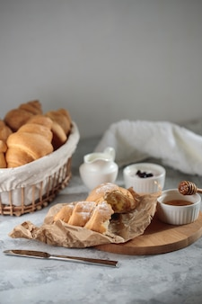 Delicious breakfast, close-up. a broken croissant with cream lies on a wooden board, with a honey bowl and a jug of cream.