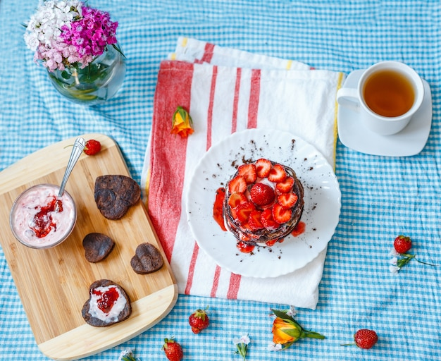 Delicious breakfast desert. stack of pancakes with fruit and strawberry jam and tea, in white plate
