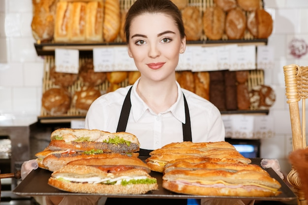 Delicious breakfast. horizontal shot of a beautiful female bakery worker holding tray full of sandwiches