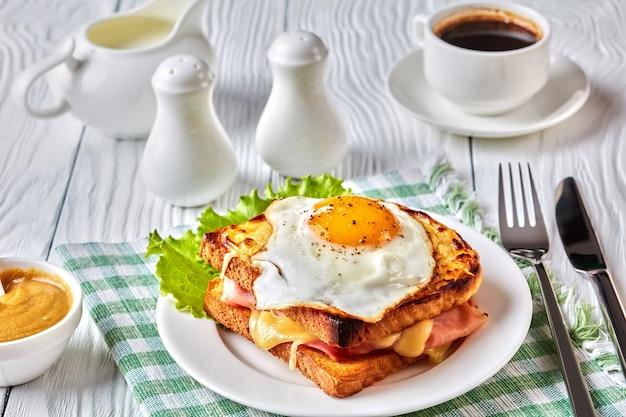 おいしい朝食-温かいフレンチトーストのクロックムッシュとハム、溶けたエメンタールチーズ、目玉焼きを白いプレートに載せ、テーブルの上にコーヒーを添えて、上からの眺め、クローズアップ