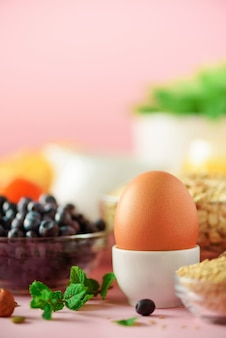 Delicious breakfast ingredients. soft boiled egg, oat flakes, nuts, fruits, berries, milk, yogurt, orange, banana, peach on pink background.