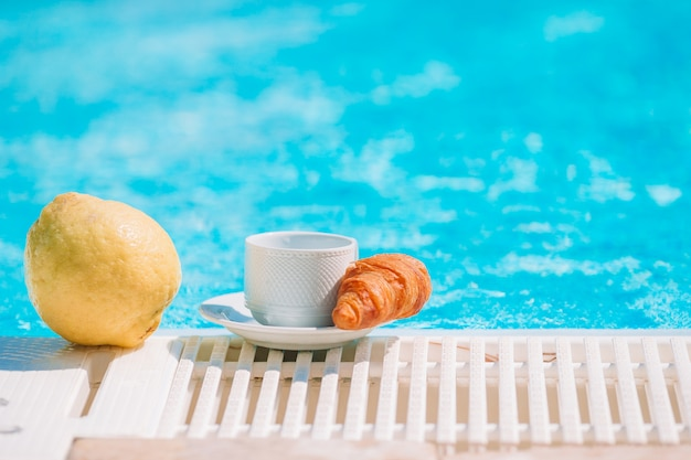 Delicious breakfast lemon, coffee, croissant by the pool