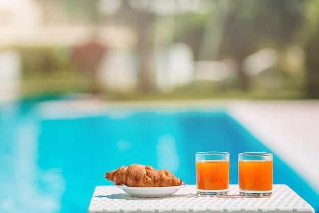 美味しい朝食レモン、コーヒー、クロワッサン、プールサイド