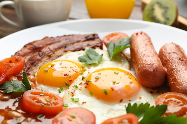 Delicious breakfast or lunch with fried eggs on wooden table, close up