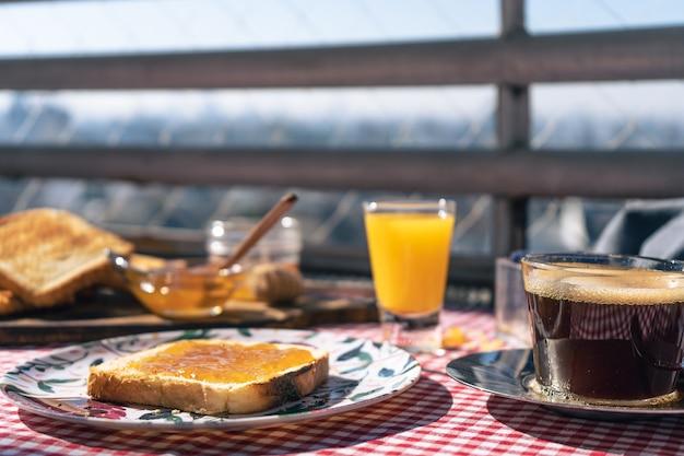 화창한 아침 분위기에서 블랙 커피, 오렌지 주스, 토스트의 맛있는 아침 식사.
