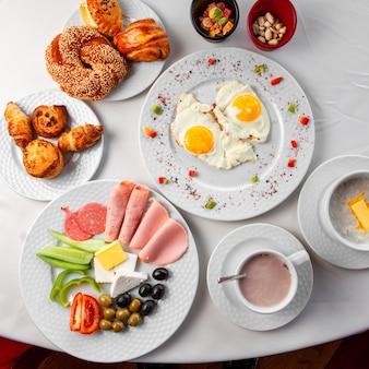 白い背景の上のサラダ、目玉焼き、ペストリーの上面とテーブルの上のおいしい朝食