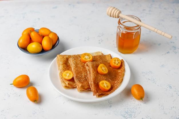 Вкусный завтрак. православный праздник масленица. блинчики с кумкватом и хонетом, вид сверху