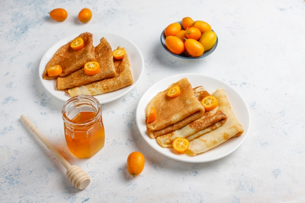 Delicious breakfast. orthodox holiday maslenitsa. crepes with cumquats and honet, top view