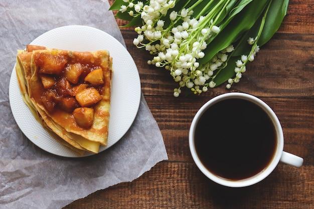 おいしい朝食。スズランのある木製のテーブルにキャラメリゼしたリンゴとコーヒーを添えたパンケーキ。