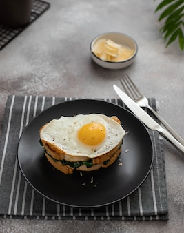 Delicious breakfast sandwich with fried egg, spinach and cheese on a dark plate. close-up