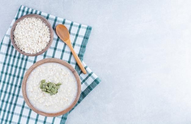 Deliziosa colazione che serve di farina d'avena con ripieno di pepitas sulla tovaglia piegata, accanto a una ciotola di avena e un cucchiaio di legno su fondo di marmo.