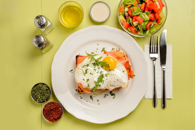 Delicious breakfast. toast with salmon, egg, salad and spices