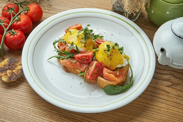 Delicious breakfast - toast with salmon, poached egg with hollandaise sauce and cherry tomatoes, served in a white plate.