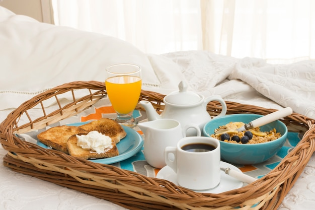 Delicious breakfast tray on bed