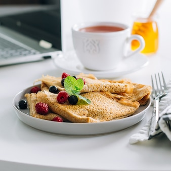 Delicious breakfast. white desktop table with laptop and fresh crepes pancakes, cup of tea