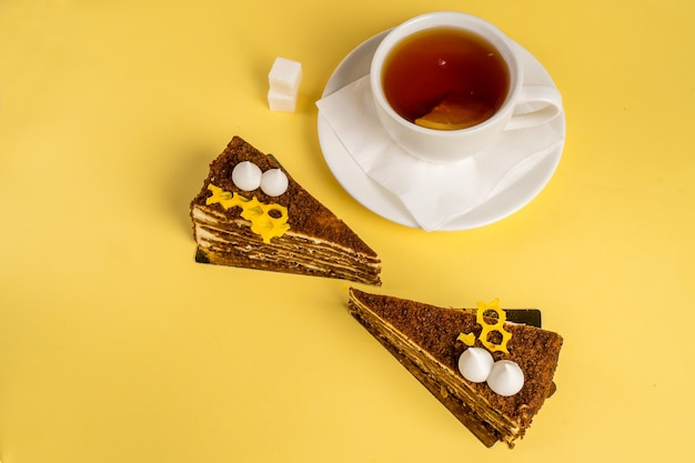 Delicious breakfast with the cake and black tea on yelow  top view copy space