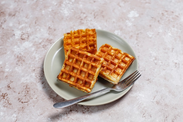Delicious breakfast with coffee, orange juice, waffles,croissants,jam,nut paste on light ,top view