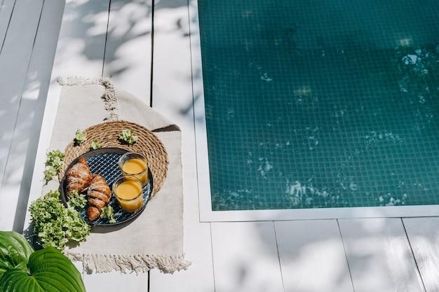 2人分の屋外プールの朝食の近くでクロワッサンとオレンジジュースを使ったおいしい朝食