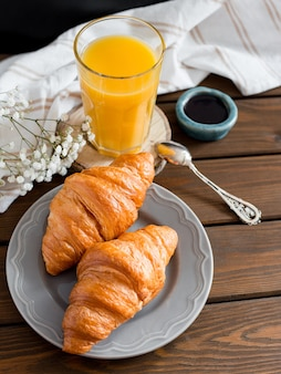 Delicious breakfast with croissants, flowers and juice, good morning