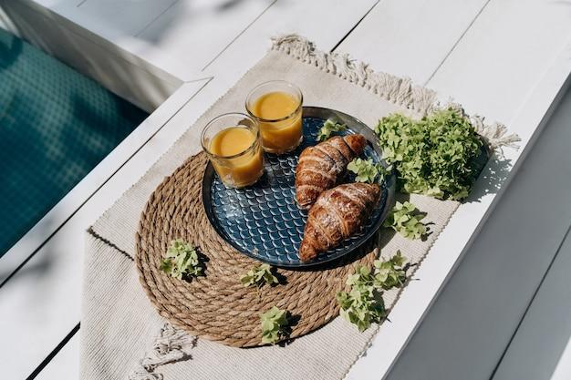 美味的早餐与羊角面包和橙汁在室外游泳池早餐附近