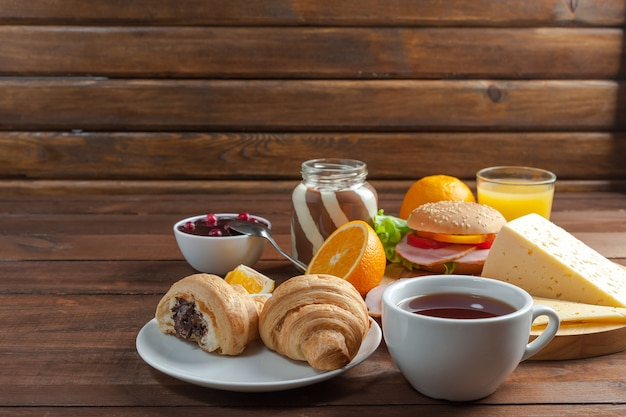 Вкусный завтрак с круассанами, бутербродами и апельсиновым соком