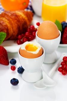 Вкусный завтрак с яйцами, свежими круассанами, фруктами и соком.