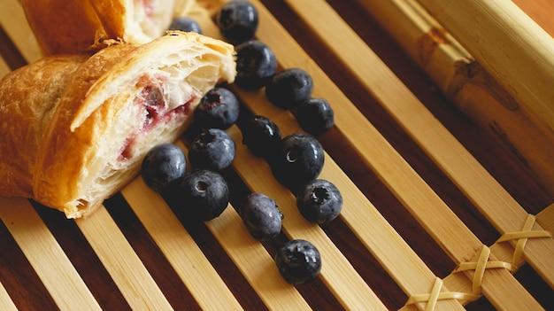 신선한 크루아상과 나무 표면에 블루 베리와 함께 맛있는 아침 식사