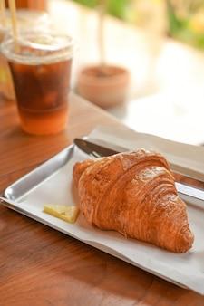 木製のテーブルに焼きたてのクロワッサンとコーヒーをバターと一緒に添えた美味しい朝食。