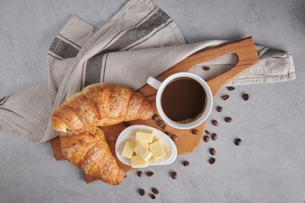 신선한 크루아상과 버터를 곁들인 커피로 구성된 맛있는 아침 식사