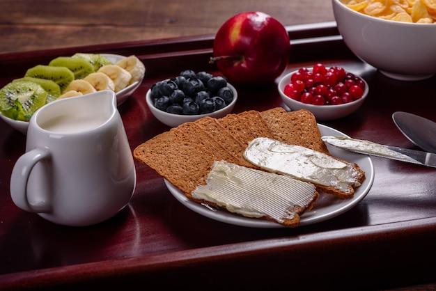焼きたてのクロワッサンと熟した果実の美しい木製のテーブルで美味しい朝食