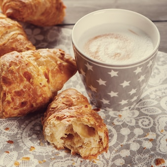 Delicious breakfast with fresh croissants and cup of cappuccino on grey wooden background