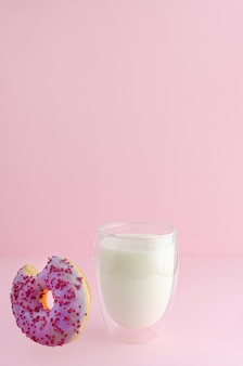 Delicious breakfast with glass of milk and falling bitten dessert on pastel pink background