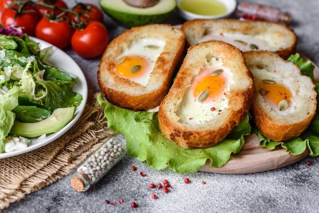 うなり声、卵、アボカド、チェリートマトのおいしい朝食。新鮮なサンドイッチと楽しい朝の食事
