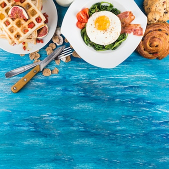 Delicious breakfast with pastries on wooden textured background