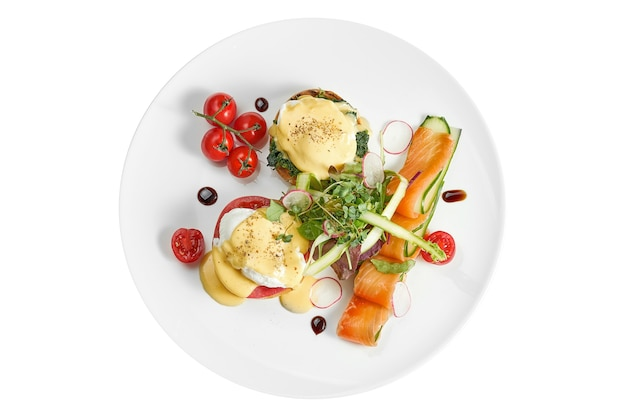 Delicious breakfast with poached egg toast and hollandaise sauce, lightly salted salmon in a white plate. isolated on white surface. view from above