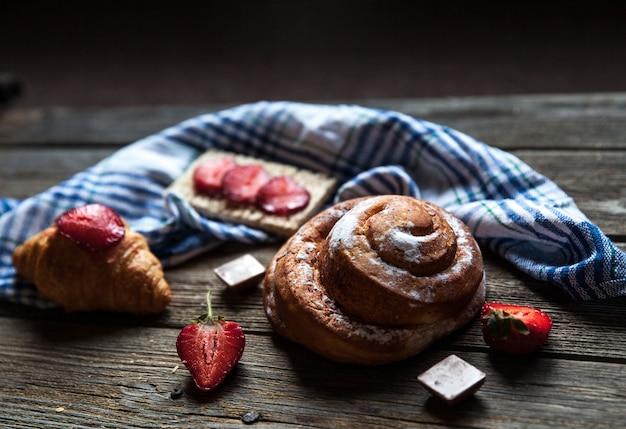 Вкусный завтрак с клубникой и сладкой булочкой на деревянном столе. фрукты, еда, шоколад