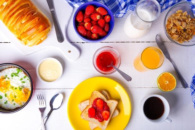 白いテーブルの上にいちごジャム、オレンジジュース、シリアル、卵とおいしい朝食