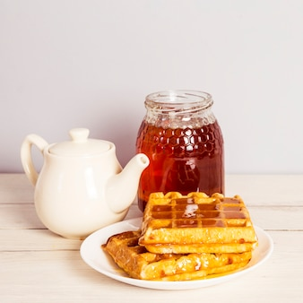Delicious breakfast with tea; sweet waffle and honey