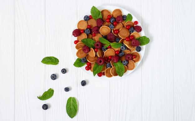 小さなミニパンケーキ、ブルーベリー、ラズベリー、赤スグリ、白い木製のテーブルにミントのおいしい朝食。オランダのpoffertjesトップビュー
