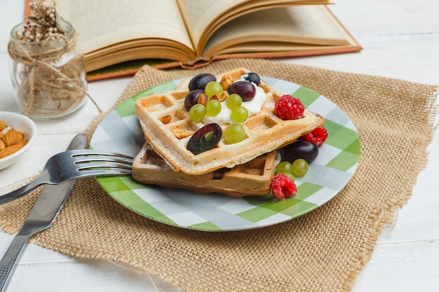 Delicious breakfast with waffles and fruits near a book