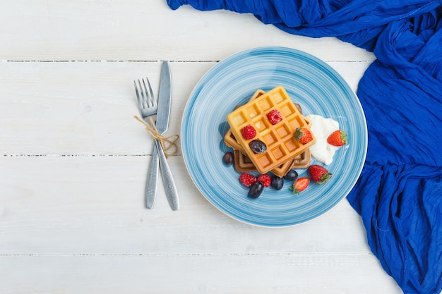Delicious breakfast with waffles and fruits