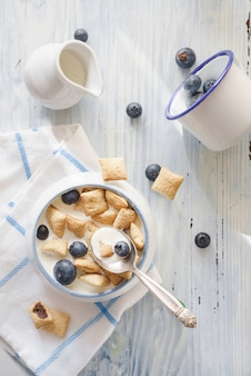 Delicious breakfast with a white ceramic mug on white table cloth