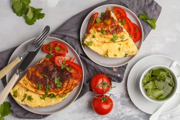 Вкусный яркий яичный омлет с сыром и овощами.