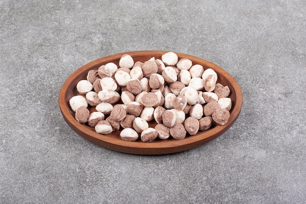 Вкусные коричневые конфеты на деревянной тарелке