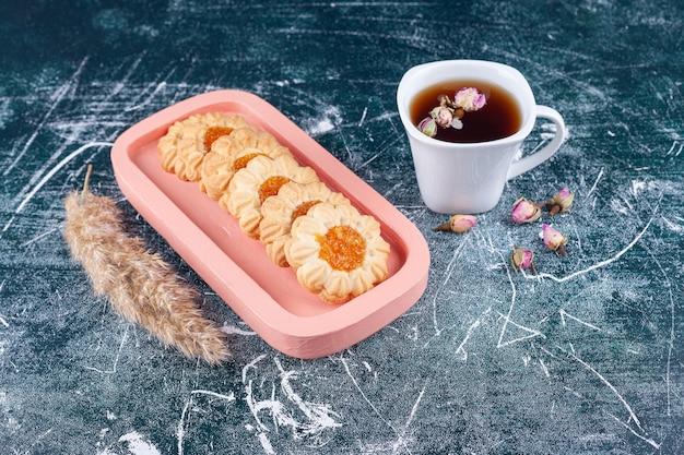 Deliziosi biscotti dorati con marmellata all'interno e una tazza di tè nero.
