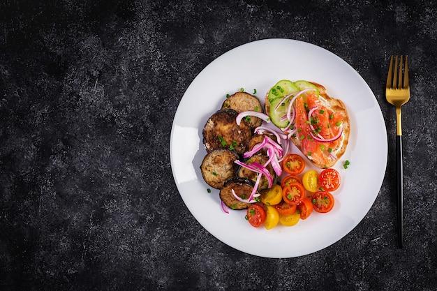 Вкусный бранч бутерброды с лососем, хлебом и сливочным сыром и рукколой, салат из помидоров на темном фоне. вид сверху, вверху